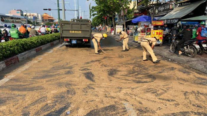 Dầu nhớt tràn ra đường, CSGT rải cát để người đi đường khỏi bị trượt Ảnh 1