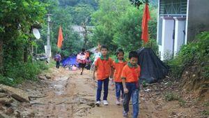 Học sinh vùng lũ lội bùn đến trường khai giảng