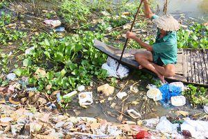 Lão nông cần mẫn làm sạch môi trường nước mùa lũ