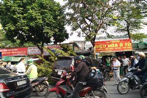 Va chạm với xe máy, xe ô tô Lexus 'hạ' đổ gốc cây trên đường phố Hà Nội