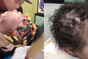 Phẫn nộ clip bé 1 tuổi bị bà đè ngửa, đổ hóa chất làm tóc xoăn ở tiệm làm đầu