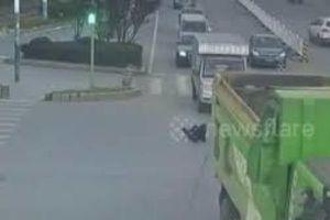 Người phụ nữ bò lồm cồm dậy sau khi bị cuốn vào gầm xe tải