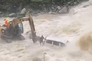 Máy xúc giải cứu tài xế ô tô bị mắc kẹt giữa dòng sông chảy xiết