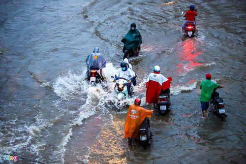 Triều cường dâng cao, người dân TP.HCM lội nước về nhà