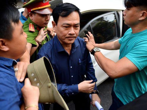 Hình ảnh bị cáo Nguyễn Hữu Linh gây chú ý khi được an ninh bảo vệ