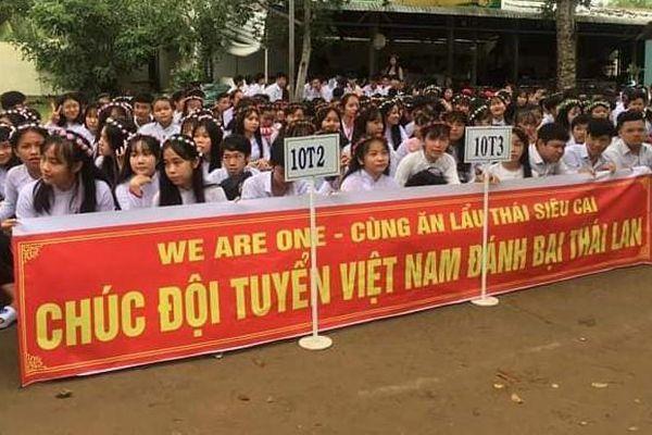 Học sinh mang băng rôn cổ vũ đội tuyển Việt Nam đến lễ khai giảng