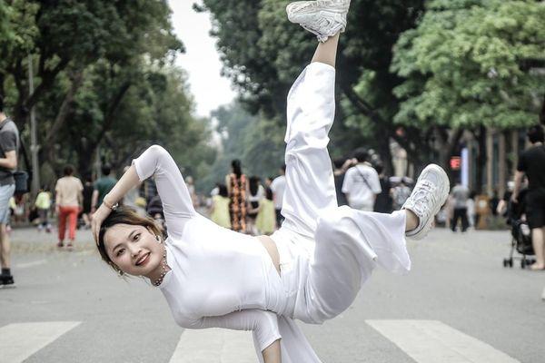 Cô gái mặc áo dài, tạo dáng hip hop trên phố đi bộ