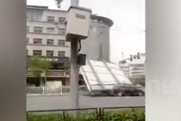 Biển quảng cáo rơi đè bẹp xe hơi đang đi trên đường ở Trung Quốc