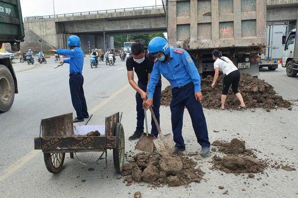 Hình ảnh đẹp: TTGT giúp xe tải gặp sự cố đổ đất thải ra đường