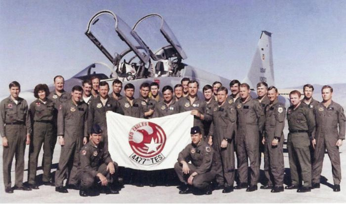 """The """"Red Eagle"""" pilots pose for a photo with a flag bearing their emblem."""
